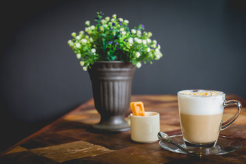 Hot art Latte Coffee in a cup on wooden table, retro and vintage