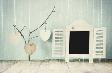 decorative chalkboard frame and wooden hanging hearts over wooden table