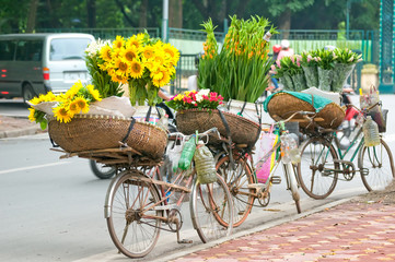 Selling flowers not red identity on the street in the early morning. Farmers use bicycle, on wearing the conical hat then go to the small lane to the florist.