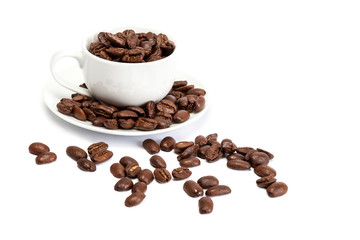 Coffee beans and ceramic cup on white background.