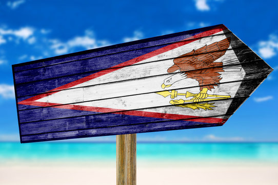 American Samoa Flag wooden sign on beach background
