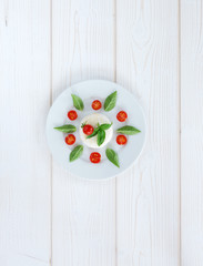 Round camembert cheese with cherry tomatoes and basil on a round white plate. top view