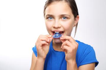 Fototapeta Dziewczynka zakłada aparat ortodontyczny na zęby obraz