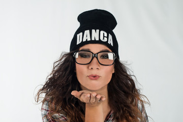 Portrait of young beautiful brunette dancer girl wearing glasses and black hipster hat sending blow kiss