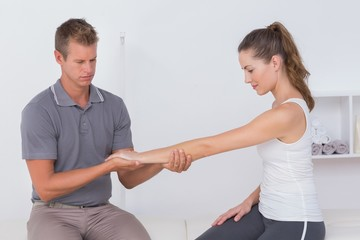 Doctor stretching a young woman arm