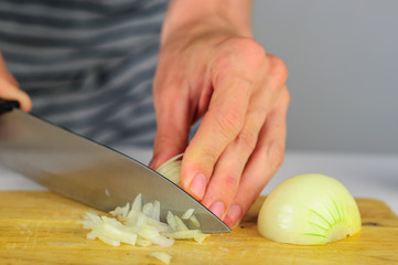 Man hands cutting onion