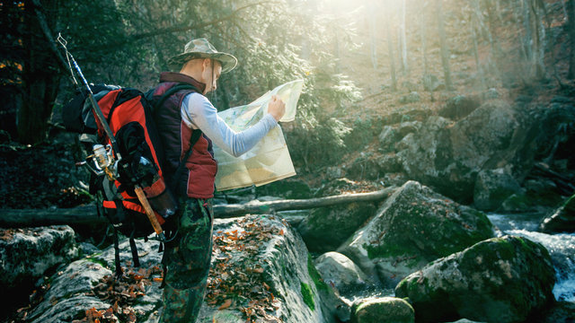 Walking hiker looking at map. Hiking in beautiful autumn forest.