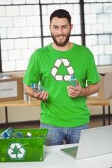 Portrait of man holding bottles in office