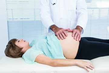 Doctor touching stomach of pregnant woman