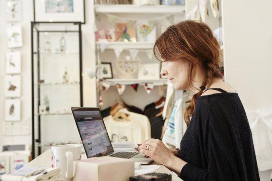 Woman using laptop inn gift shop