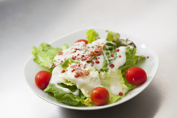Caesar salad with white dressing served on a white bowl