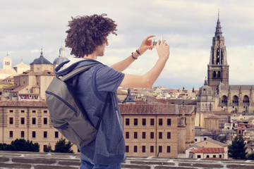 Tourist young man with backpack taking picture