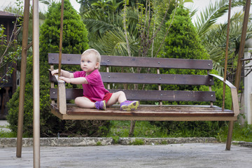 baby girl sits on  swing in park