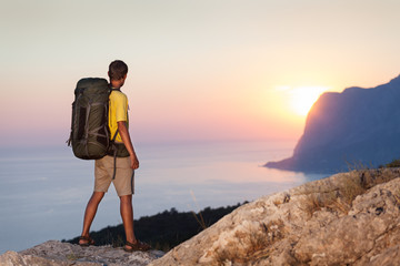 Man with backpack and looking at sunrise