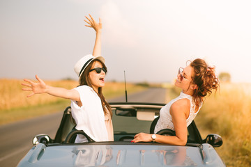 Two happy female friends enjoying road trip in their cabriolet