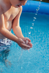 Happy child playing with water in the pool