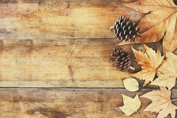 top view image of autumn leaves and pine cones over wooden textured background