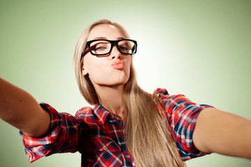 Close up portrait of a young kissing blonde girl holding a smartphone digital camera with her hands and taking a selfie self portrait of herself standing against blue background