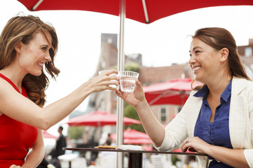 Friends sitting at an outdoor table raising drinks in a toast.