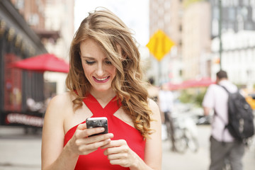 An attractive young woman smiling and looking at her mobile phone.
