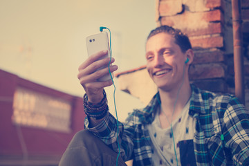 Young and smiling man on the roof, looking at mobile phone and listening music (intentional vintage color, focus on mobile phone)