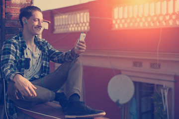 Young and smiling man sitting on the roof with mobile phone and listening music (intentional sun glare and vintage color, focus on mobile phone)
