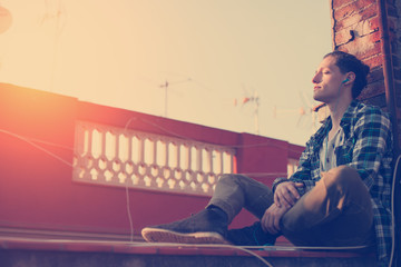 Young and handsome man relaxing on the roof and listening music on his mobile phone (intentional sun glare and vintage color)