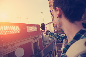 Brave young traveler man doing photo with mobile phone on the roof (intentional sun glare and vintage color, focus on mobile phone)