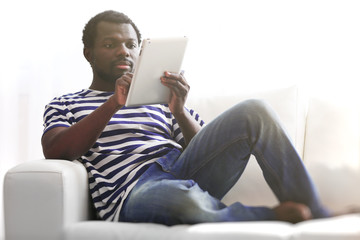 African American man with tablet and credit card on sofa in room