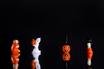 Halloween figures aligned shot front on on a black background with reflection
