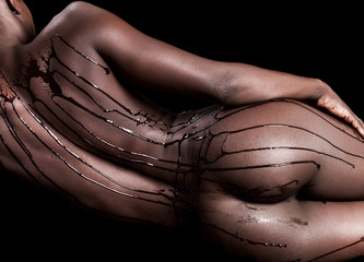 Sensual woman naked body covered with chocolate drops