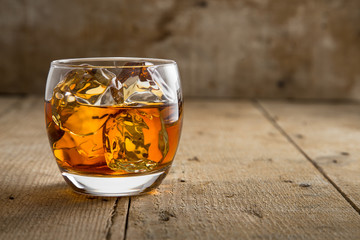 Modern glass of scotch whisky old vintage wooden barrel background lifestyle pub fine art craft bourbon
