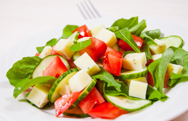 Fresh salad with tomatoes, arugula, cucumber and cheese cubes