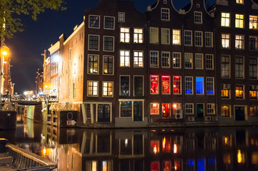 Red light district at night, the Church of St. Nicholas is visible in the distance, the Netherlands.