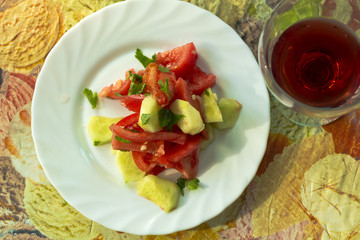 Salad of tomatoes and cucumbers with a glass of wine.The view from the top.