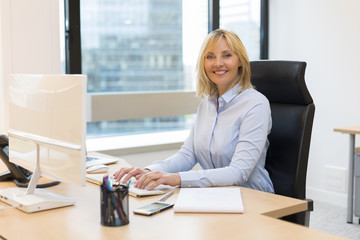 Middle aged business woman working at office