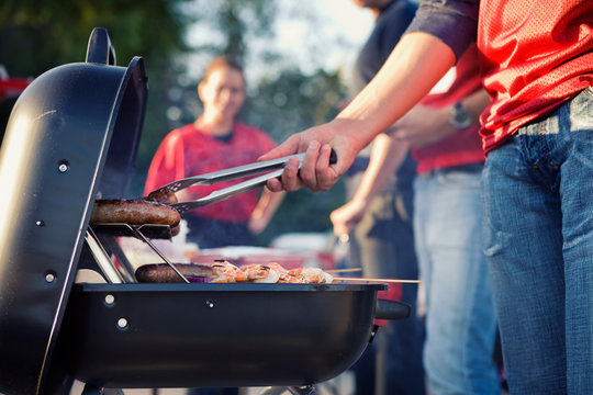 Tailgating: Man Grilling Sausages And Other Food For Tailgate Pa