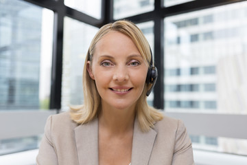 Smiling Businesswoman in the office on video conference, headset