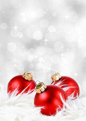Christmas background with red ornaments on feathers against a festive sparkling silver background