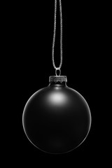 Hanging black Christmas ornament on a black background. Low key.