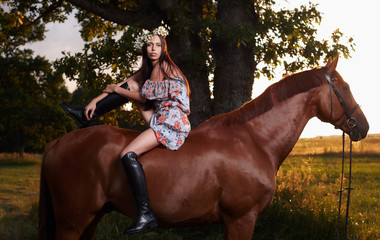 Awesome female in colorful dress sitting on brown horse.