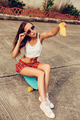 beautiful sexy young lady in erotic mini skirt with a skateboard