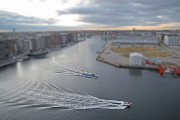 Wide canal in Copenhagen South area, Denmark, with speed boat and tour boat with miniature effect