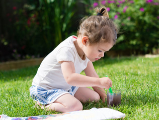 Little toddler girl painting in the garden