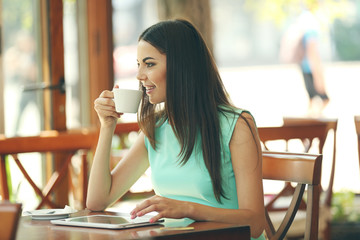 Beautiful young woman with digital tablet in cafe