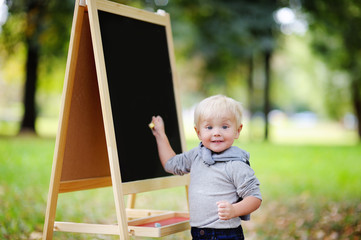 Beautiful toddler boy standing by a blackboard