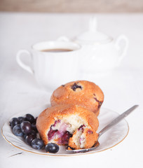 Two blueberry muffins on the white  table