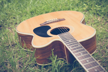 Acoustic guitar on grass with vintage tone and soft focus