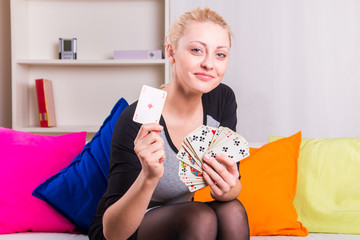 Pretty and young woman playing cards
