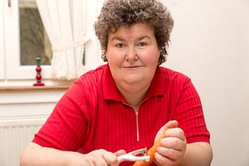 Geistig behinderte Frau schält Karotten